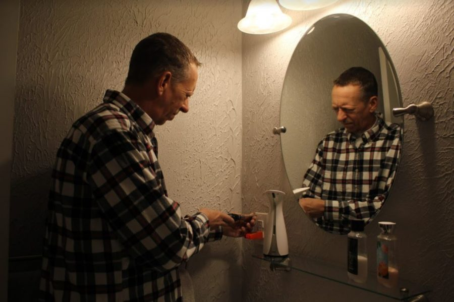 Coppell handyman Matt Young repairs a power outlet in his bathroom on Wednesday. Young has been a handyman in Coppell for 11 years after writing software applications for the finance industry.