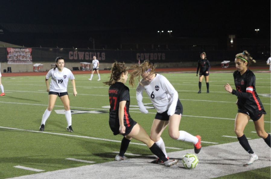 Marcus freshman midfielder Maddie Reynolds blocks Coppell sophomore defender Tatum Escobar on Friday at Buddy Echols Field. The Cowgirls defeated the Marauders, 2-1. Photo by Tanvee Patil