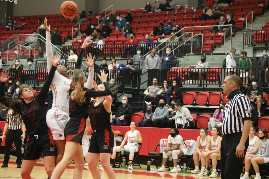 Coppell junior center India Howard defends against Marcus junior small forward Hailey Vela, senior center Alex Warren and  junior point guard Abbie Barr on Jan. 22 at the CHS Arena. The Cowgirls held the lead in all four quarters, ending with a 51-40 win over the Marauders.