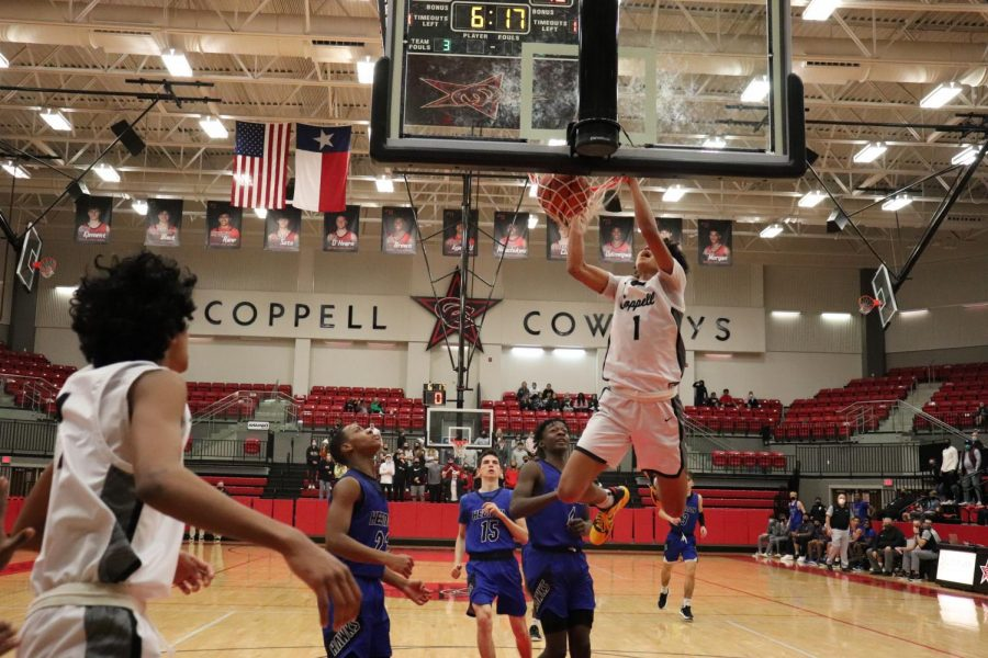 Coppell junior point guard Anthony Black dunks in the match against Hebron on Tuesday in the CHS Arena. The Cowboys defeated Hebron, 66-56.