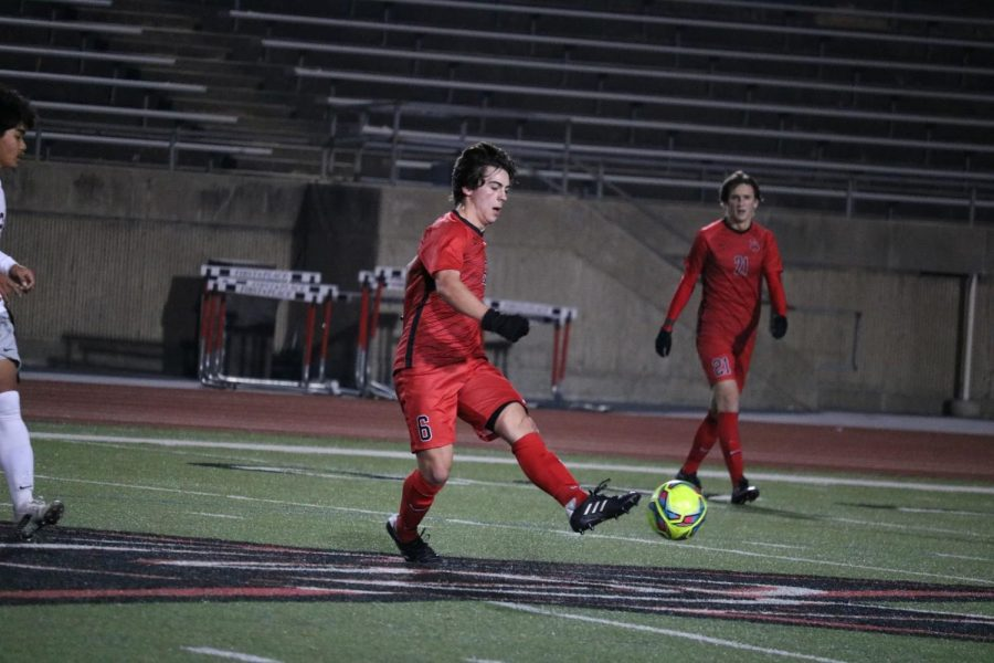Coppell+senior+defensive+mid+Garret+Greaves+passes+against+Lewisville+on+Feb.+9+at+Buddy+Echols+Field.+Coppell+soccer+was+paused+due+to+inclement+weather+this+week+but+returns+to+play+next+week.
