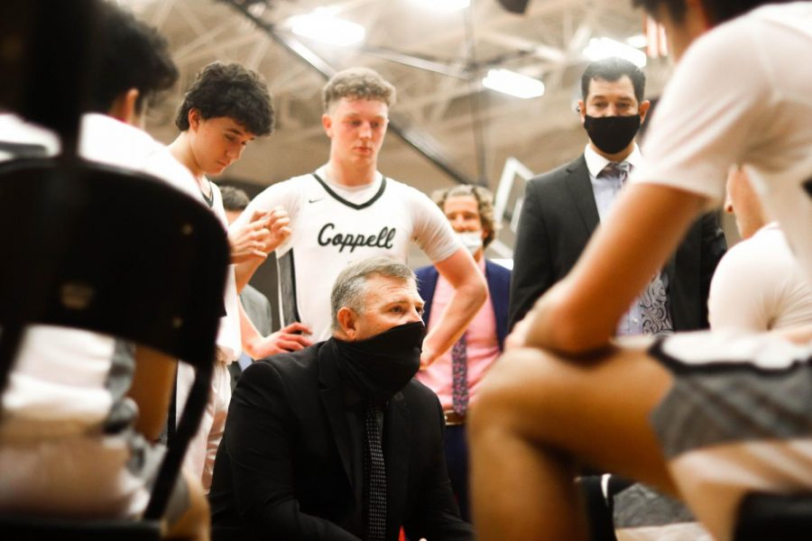 Coppell coach Clint Schnell discusses a game plan with the Cowboys prior to overtime against Lewisville on Friday in the CHS Arena. The Cowboys defeated the Farmers in overtime, 70-65, to keep possession of first place in District 6-6A.
