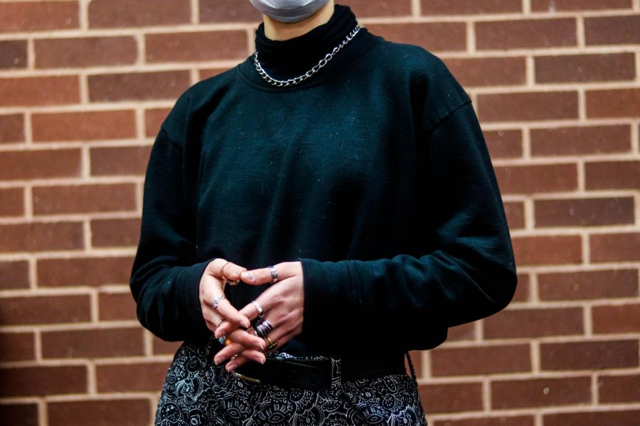 Coppell High School senior Elena Hewett wears patterned pants, a turtleneck, a chain and an assortment of rings at CHS on Thursday. Students at CHS went from wearing supporter shirts and Lululemon to mom jeans and Doc Martens since the pandemic.