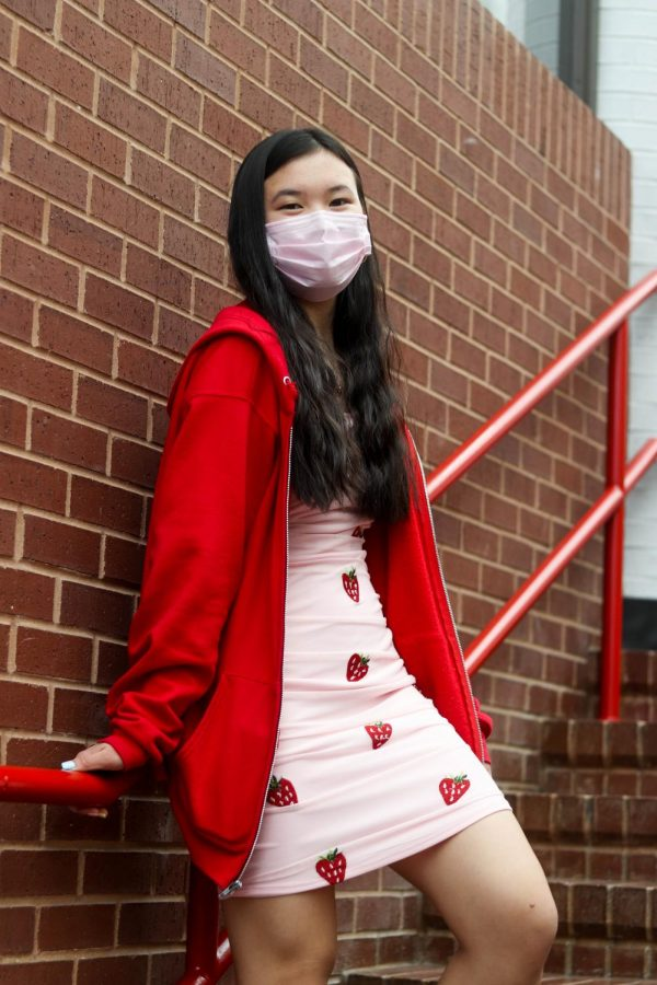 Coppell High School sophomore Jia Rosenbaum wears a strawberry-patterned minidress and red sweater at CHS on Thursday. Students at CHS went from wearing supporter shirts and Lululemon to mom jeans and Doc Martens since the pandemic.