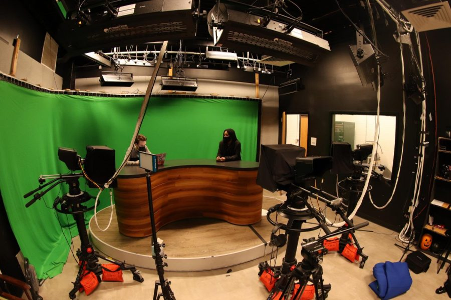 Coppell High School seniors Mark Suante and Hailey Wilkins go over some graphic designs in the  KCBY-TV Studio on Dec. 7. Journalism is allowing students to become increasingly involved in the community. Photo by Lilly Gorman