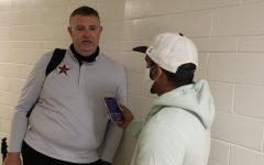 The Sidekick co-sports editor Meer Mahfuz interviews boys basketball coach Clint Schnell after Coppell's Class 6A area playoff loss against Lake Highlands at Loos Sports Complex on Thursday. While others find sports coverage difficult, Mahfuz thinks sports coverage helps him escape the teenage world.