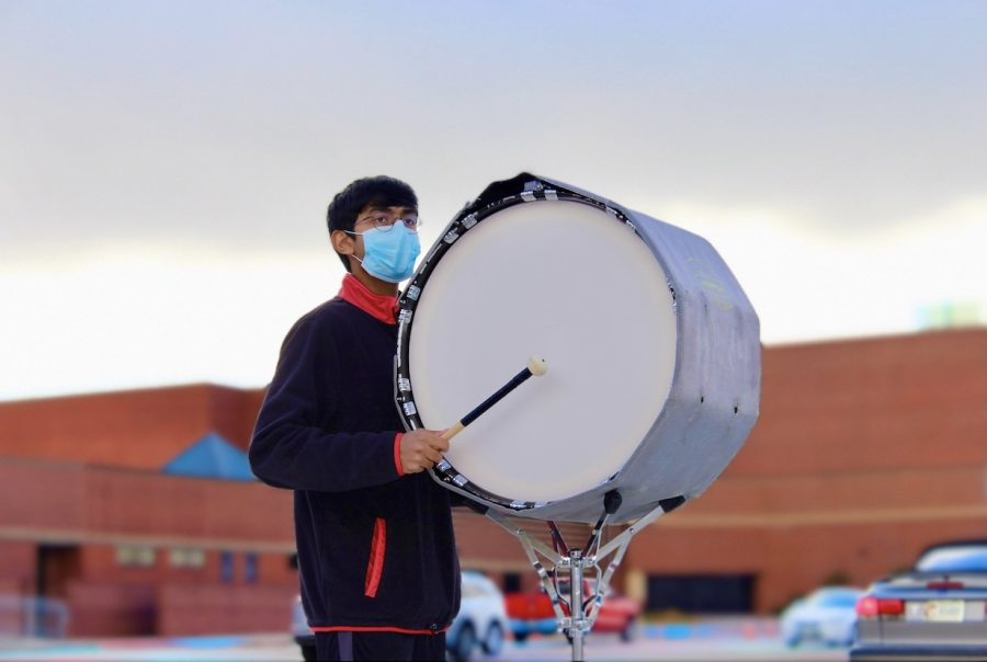 Coppell High School senior Akhil Aitha plays the marching bass drum on Feb. 8 in the CHS parking lot outside the band hall. In addition to percussion, Aitha makes music outside of school by singing and producing beats on his computer.