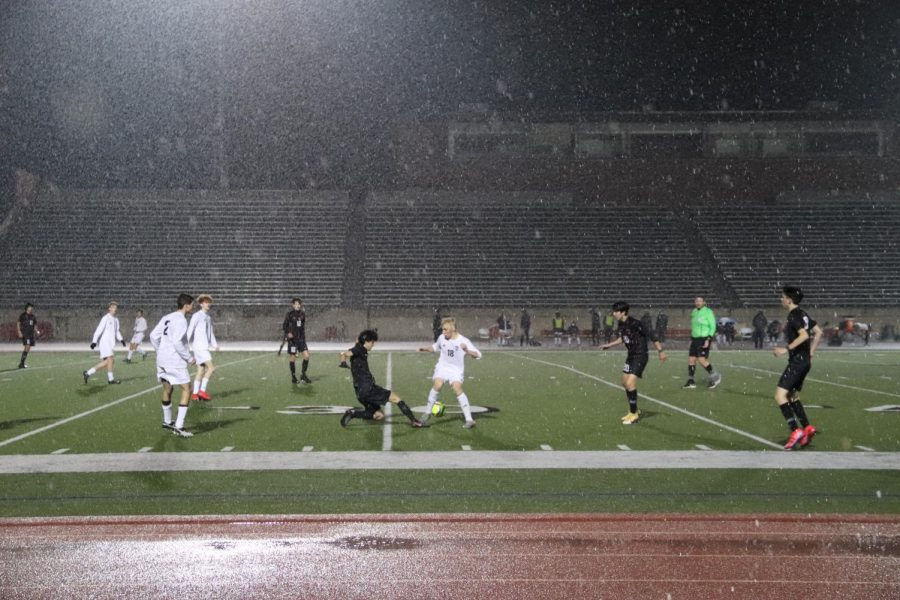 Coppell sophomore forward Alejandro Reyes goes in for a 50-50 against Flower Mound senior defender James Chamberlain at Buddy Echols Field last night. The match experienced many lightning delays but the Cowboys eventually dropped the match, 1-0, after play was called five minutes into the second half.