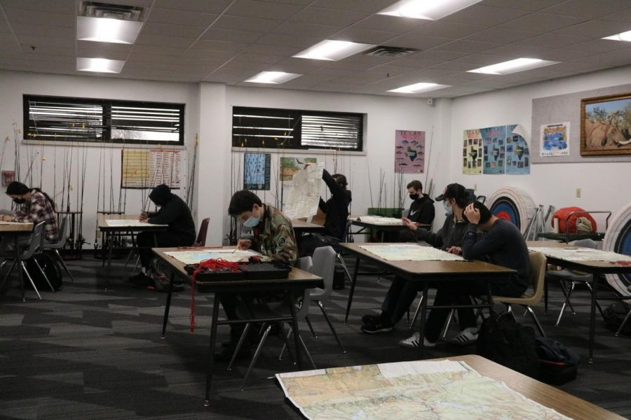 Coppell High School students work on a geographical map assignment during the second period of the Coppell outdoor adventures class with coach Bill Parker in H107. Due to the cold weather today, a lot of classes have moved to learning indoors. Photo by Tracy T.