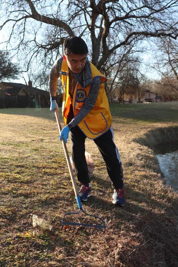 Coppell City Council Place 5 member John Jun rakes trash as a part of the Coppell Lions Club at Duck Pond Park on Saturday. Jun has been picking up trash around Coppell in an effort to better support his community.