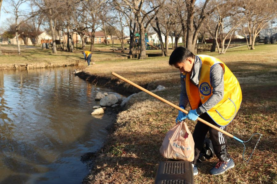 Coppell City Council Place 5 member John Jun picks up trash as a part of the Coppell Lions Club at Duck Pond Park on Saturday. Jun has been picking up trash around Coppell in a way to better support his community.
