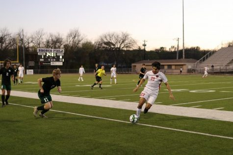 Coppell senior midfielder Sebastian Flores dribbles against Prosper senior defender Chandler Kovarik during the Class 6A bi-district playoff match  at Denton High School on Friday. The Eagles defeated Cowboys 3-1.