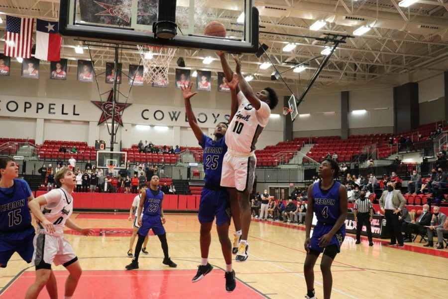 Coppell junior guard Naz Brown shoots a layup against Hebron junior forward Logan Zacarias at the CHS Arena on Jan. 26. Brown was selected to the first team of All-District 6-6A.