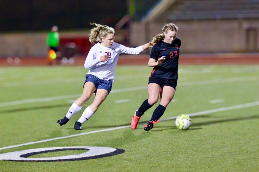 Coppell junior midfielder Bailey Peek shields against Plano junior midfielder Lexie Moore on Monday night at Buddy Echols Field. The Cowgirls tied the Wildcats, 1-1.