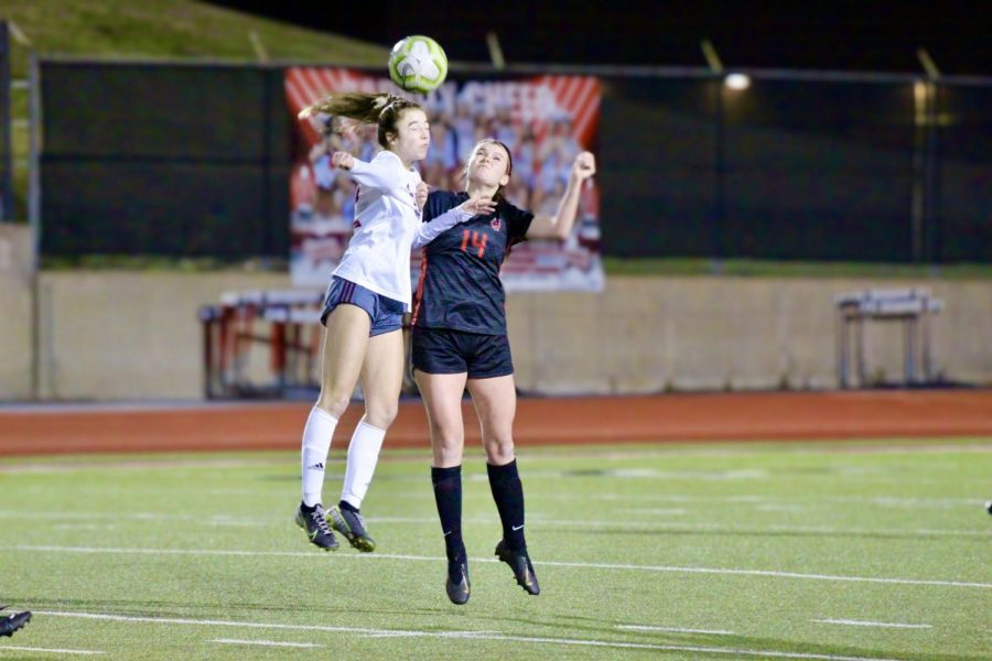 Coppell junior defender Claire Yaney and Plano senior forward Amanda Walsh go for a header at Buddy Echols Field on Monday.  The Cowgirls tied with the Wildcats, 1-1.