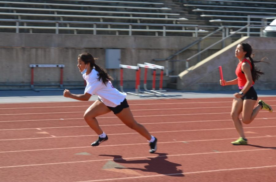 Coppell junior runner Aunna Aguirre and sophomore runner Lillian Egger practice relays at Buddy Echols Field on Thursday. On Friday and Saturday, the Coppell girls track and field team placed second at the District 6-6A Meet, while the Coppell boys placed fifth.