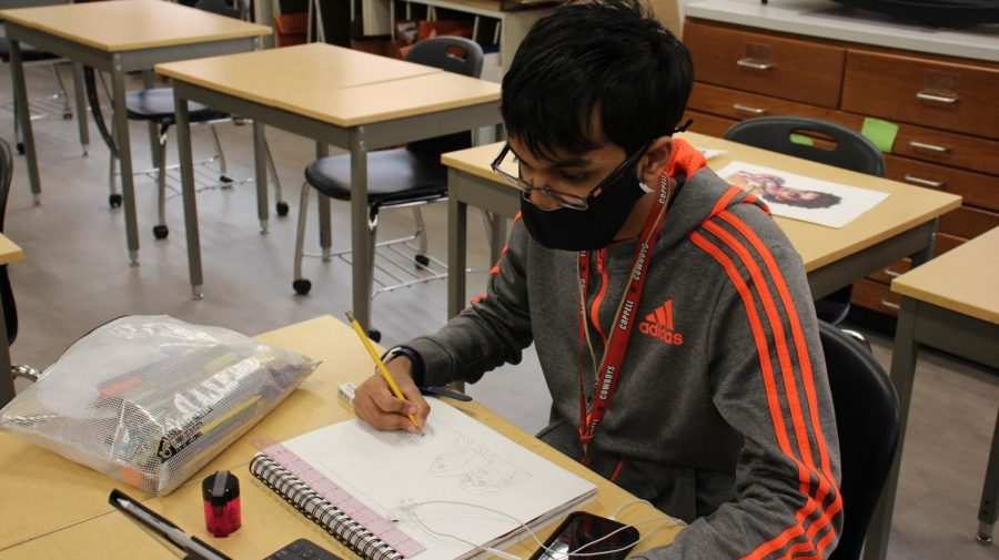 Coppell High School senior Vinay Munagapati draws a portrait in AP drawing teacher Michelle Hauske's second period on Thursday. Munagapati is working on a horror maze video game and will pursue video game design at the University of Texas at Dallas in the fall.