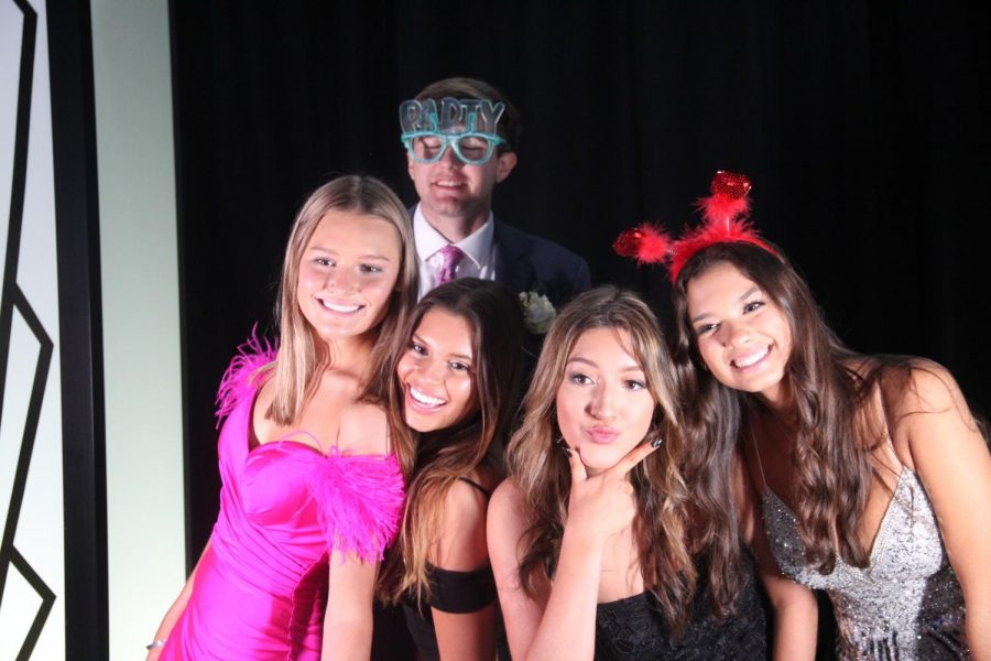 Coppell High School seniors Anabelle Sigman and Eric Angyal, Ursuline Academy senior Pamela Arias and CHS seniors Maddie Strum and Ana Alvarez strike a pose in front of the photo booth at prom in the CHS Arena. Due to a decrease in COVID cases and increase in vaccinations, CHS seniors attended a senior prom photo shoot on May 1in the CHS arena.