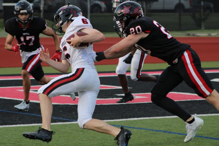 Coppell+sophomore+quarterback+Zach+Darkoch+evades+Coppell+junior+Brayden+Axe+to+score+a+touchdown+on+Friday+at+Buddy+Echols+Field.+The+Coppell+football+team+played+an+intrasquad+spring+game%2C+divided+into+offensive+White+Team+and+defensive+Black+Team.+