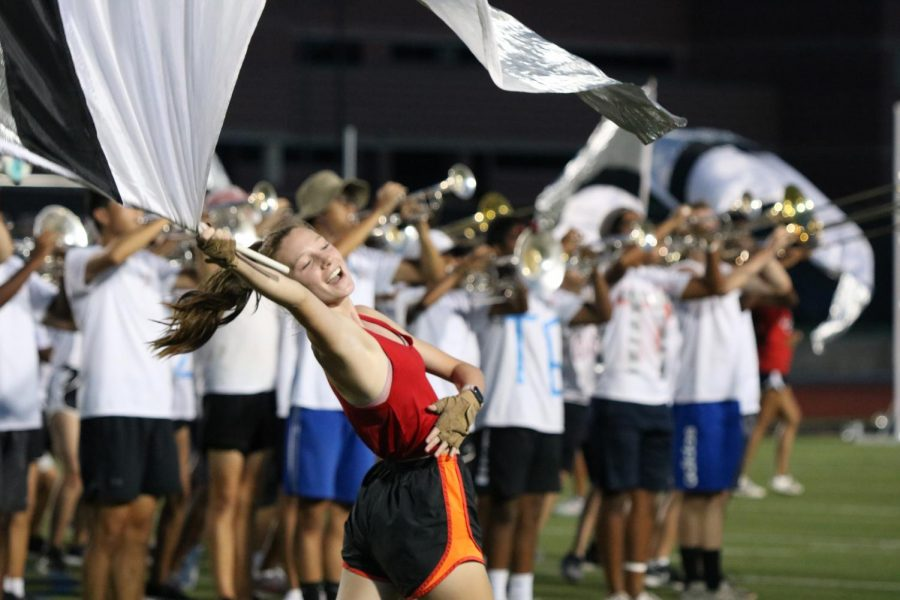 """Coppell High School junior color guard captain Audrey DePew performs in the marching band's production """"Carousel""""  at Buddy Echols Field on Saturday. The band, drumline and color guard premiered their 2021 productions in the parent preview after the Cowboy Cookout at 7:30 p.m."""