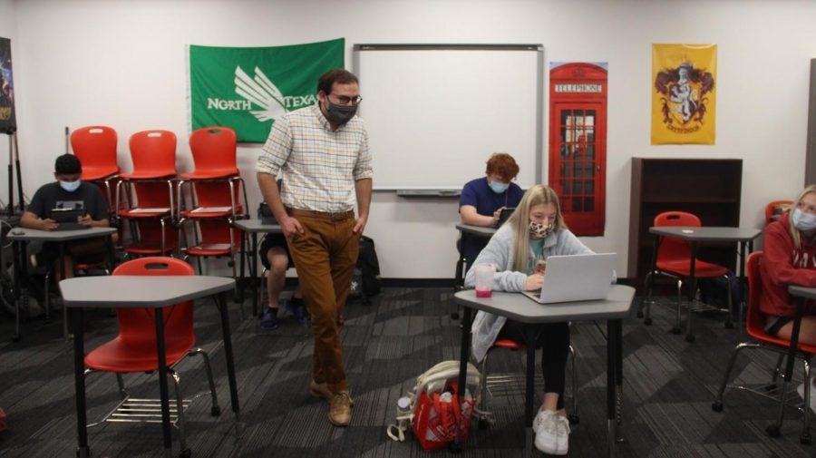 Coppell+High+School+English+II+teacher+Stephen+Patino+assists+CHS+sophomore+Macy+Baume+during+fifth+period+in+his+classroom+on+Oct.+19.+Due+to+the+evolving+COVID-19+situation%2C+the+mandatory+mask+mandate+will+be+reinstated+for+grades+pre-K+through+grade+12+while+a+temporary+virtual+schooling+option+is+available+for+pre-K+through+grade+for+the+first+nine+weeks+of+school.+