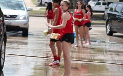 CHS9 student Kyndal Ritch waves forward a round of cars during the Lariettes car wash fundraiser in the Sprouts parking lot on Sandy Lake Road on Saturday. The Lariettes held the car wash to fund their seasonal contest costumes. Photo by Olivia Cooper