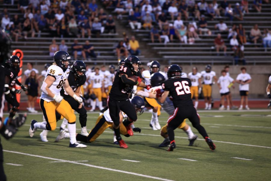 Coppell junior running back Blake Robbins evades Highland Park senior defensive lineman Jack Curtis at Buddy Echols Field on Sept. 10. The Cowboys host Plano at Buddy Echols Field on Friday to kick off district play at 7 p.m.