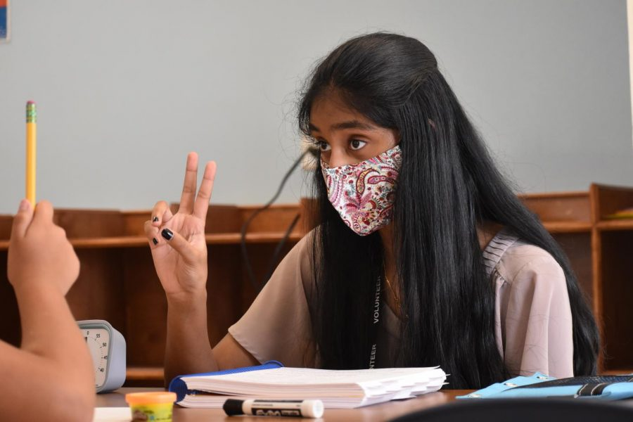 Coppell High School senior Veda Kanamarlapudi teaches a fourth grade student how to speak and write English at Wesley Rankin Community Center in Dallas on Sept. 18. Kanamarlapudi volunteers to teach English as second language students how to read and write.