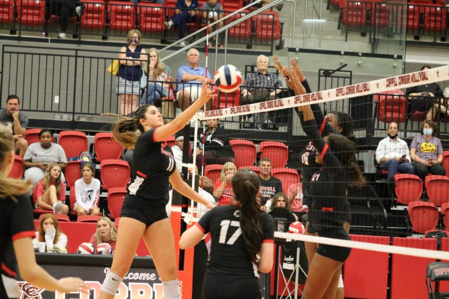 Coppell senior middle blocker Aley Clent tips against Euless Trinity in the CHS Arena on Tuesday. As Coppell middle school volleyball players watched, the Cowgirls swept the Trojans, 25-11, 25-21, 25-10.
