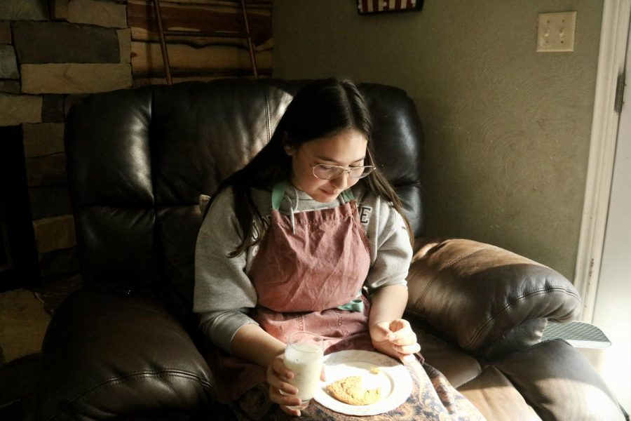 """New Tech High @ Coppell freshman Issi Neufeld enjoys a chocolate chip cookie with a glass of milk in her living room on Oct. 10. Over the years, Neufeld has gained competitive baking experience on Season 5 of the """"Kids Baking Championship"""" and Season 9 of """"Chopped Junior""""."""