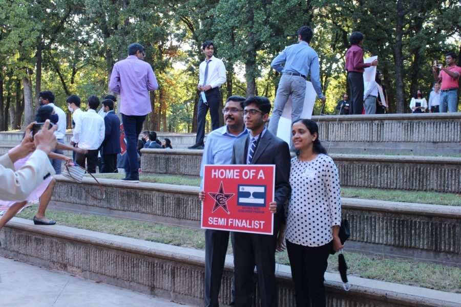 Coppell High School senior Adarsh Pulasseri, with his parents Santhosh Perincheri Karunakar and Jayalakshmi Nair, holds a yard sign outside of the CHS Library at the National Merit Semifinalists Recognition on Oct. 4. National Merit Semifinalists have the opportunity to earn the honor of National Merit Finalist and scholarships.