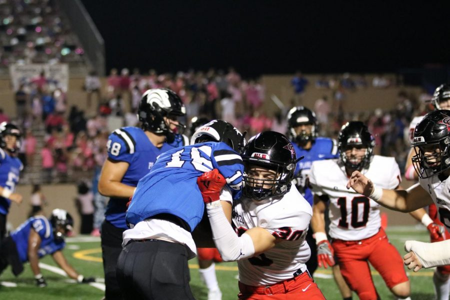 Coppell freshman free safety Weston Polk tackles Plano West senior wide receiver Resse Gunby at John Clark Stadium last night. The Cowboys defeated Plano West, 34-7.