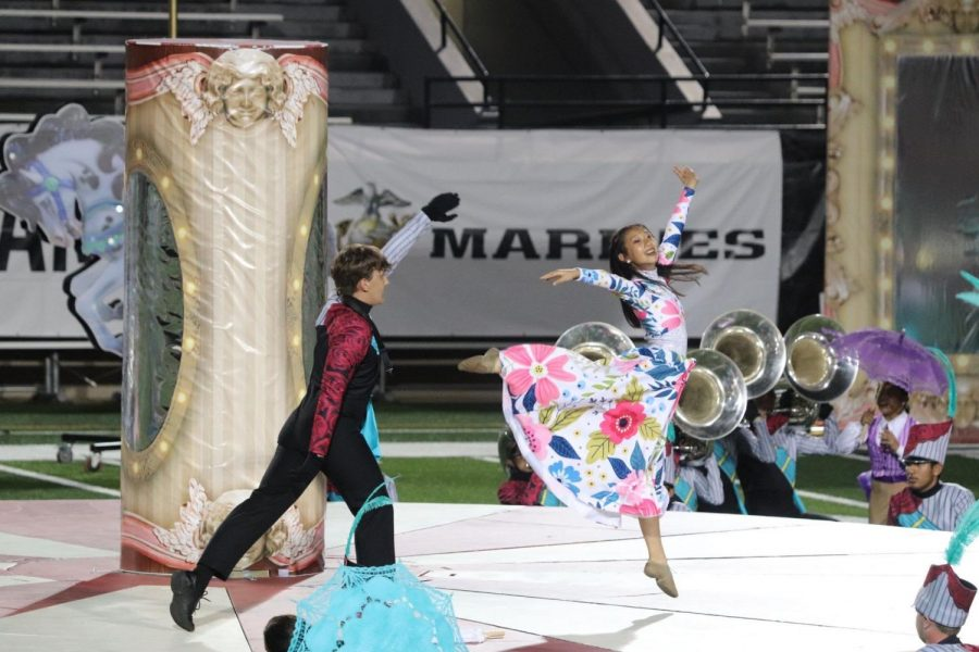 """Featured dancer senior Mira Jiang performs a sauté arabesque alongside senior Veeti Tuppurainen during the finals performance of """"Carousel"""" at the 2021 Bands of America Super Regional Championships at Pennington Field in Bedford on Saturday. The band took fifth place in the BOA Super Regional Championships."""