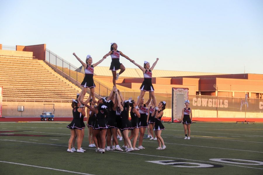 Coppell cheerleaders perform their routine at the homecoming pep rally at Buddy Echols Field on Sept. 22. Coppell High School hosted the homecoming community pep rally, which included a parade of co-curricular and extracurricular programs as well as performances by CHS's fine arts programs. Photo by Sruthi Lingam
