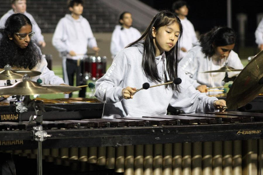 """Coppell High School junior Claire Wang plays the marimba while performing """"Birds Requiem"""" at Pennington Field in Bedford on Sept. 18. The varsity drumline won second place at the Hurst Euless Bedford Drumline Competition."""