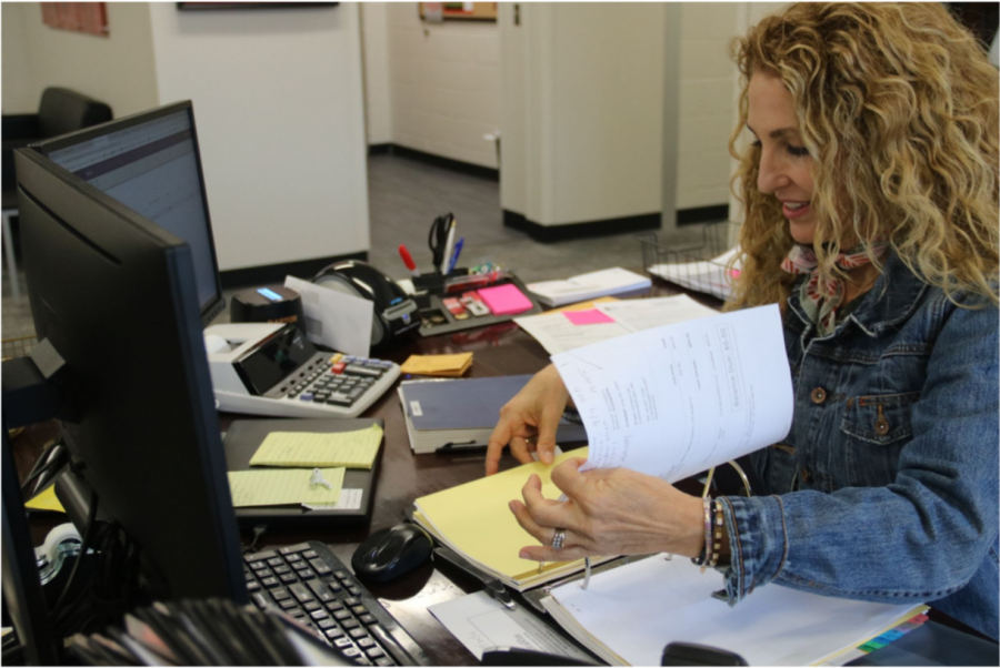 Coppell+ISD+athletic+secretary+Jessica+Hayden+finishes+work+at+her+desk+by+taking+phone+calls+and+analyzing+budget+forms.+Hayden+manages+the+budgets+for+the+athletic+and+fine+arts+department.